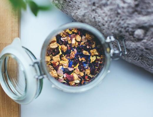Dodatek do tekstu o tym, Dlaczego lubimy chorować. Przedstawia sypaną, owocową, kolorową herbatę w szklanym pojemniku na stole. Obok leży ciepły sweter i stoi kwiat, którego liście widać w kadrze.