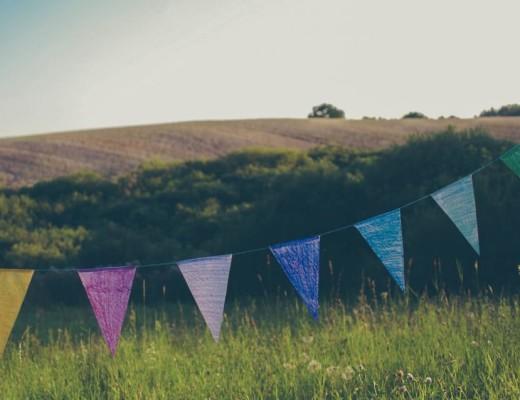 Dodatek do tekstu Życie, które uległo zniszczeniu. Przedstawia dziecięce ozdoby urodzinowe - kolorowe trójkąty zawieszone na sznurku w ogrodzie.