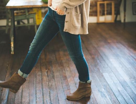 Dodatek do tekstu o tym, jak ograniczyć liczbę znajomych. Przedstawia kobietę - od brzucha w dół. Trzyma ręce w kieszeni dżinsów i kroczy przed siebie po drewnianej podłodze. Ma na sobie sweter i buty z kożuszkiem. Tło wygląda jak przytulna kawiarnia lub salon.