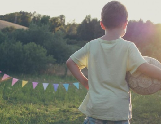 Tekst o tym, Dlaczego warto mieć pasję? Obraz przedstawia kilkuletniego chłopca, trzymającego w ręce piłkę przy blasku zachodzącego słońca.