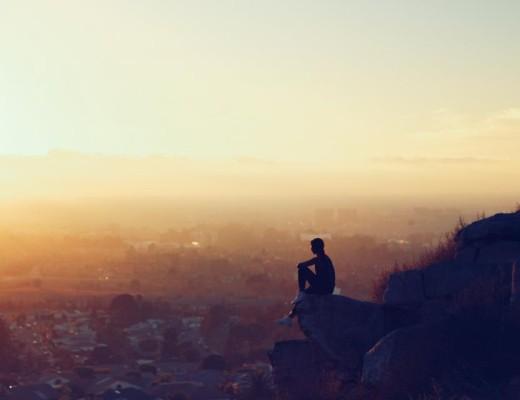 Dodatek do tekstu o tym, jak przestać bać się wojny. Przedstawia człowieka siedzącego na wzgórzu i przyglądającego się wschodącemu słońcu nad miastem.
