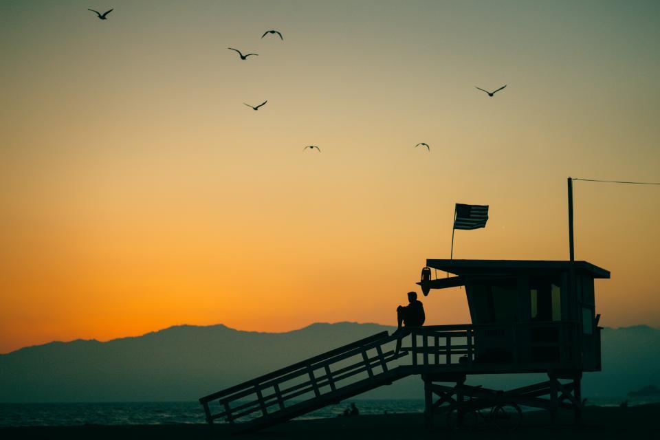 Dodatek do tekstu Najpiękniejszy poranek w roku. Przedstawia mężczyznę siedzącego na wieży widokowej nad morzem o wschodzie słońca.