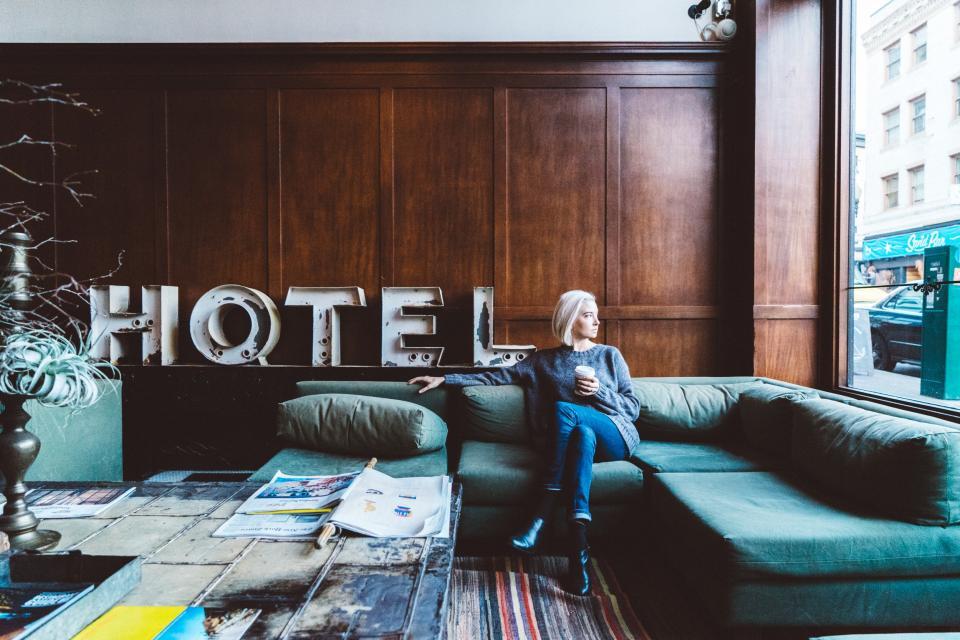 """Dodatek do tekstu o tym, że zawsze marzyła mi się kawalerka. Przedstawia kobietę siedzącą na wersalce i patrzącą w okno. Pije kawę. Za nią, na ozdobionej drewnem ścianie widać napis """"HOTEL""""."""
