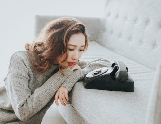 Dodatek do tekstu: Nigdy nikogo nie kochałam mocniej. Przedstawia kobietę o azjatyckiej urodzie wpatrzoną w telefon z tarczą i słuchawką - jak dawniej. Opiera brodę o ręce, które trzyma na jasnej kanapie,. Widać, że czeka, aż ktoś zadzwoni.