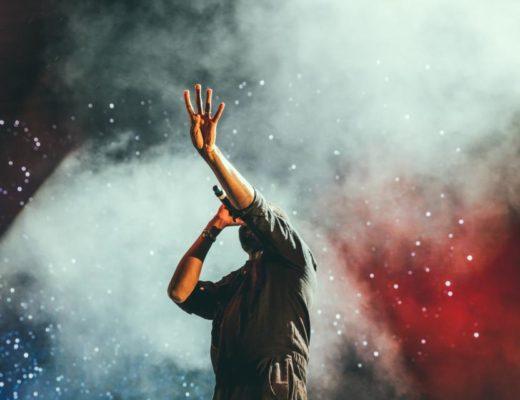 """Dodatek do tekstu o """"Kult marzeń"""". Przedstawia wokalistę skąpanego w kłębach dymu na scenie. Śpiewa i unosi rękę do góry."""