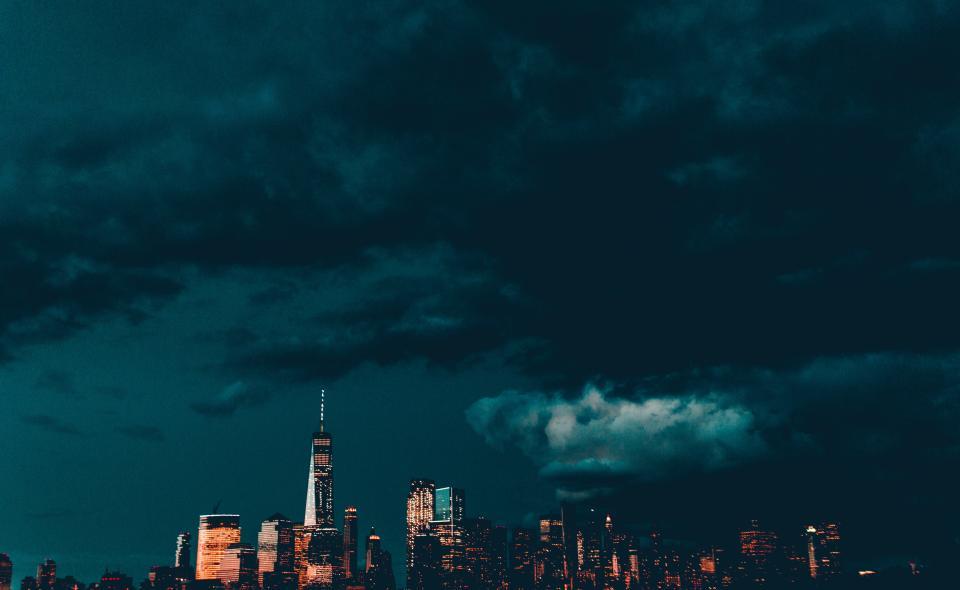 Dodatek do tekstu o tym, dlaczego warto mieszkać w Krakowie. Przedstawia nocne miasto i unoszące się nad nim ciemne, burzowe chmury. Niżej widać budynki, oświetlone tak, że łatwo dostrzec ich kolor.