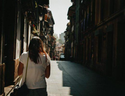 """Dodatek do tekstu """"Zawsze trochę w tyle"""". Przedstawia kobietę w białej bluzce idącą samotnie przez wąską, pustą uliczkę starego miasta."""