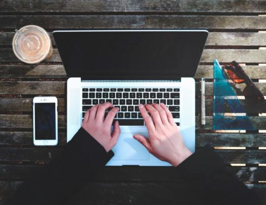 Obraz przedstawia dłonie, które stukają w klawiaturę laptopa na ślicznym, ciemnym, drewnianym tle biurka. Po lewej stronie leży smartfon i stoi plastikowy kubek z kawą. Po prawej leży ekierka i okulary przeciwsłoneczne. Dodatek do tekstu o tym, jak wskoczyć z B2 na C1 z angielskiego.