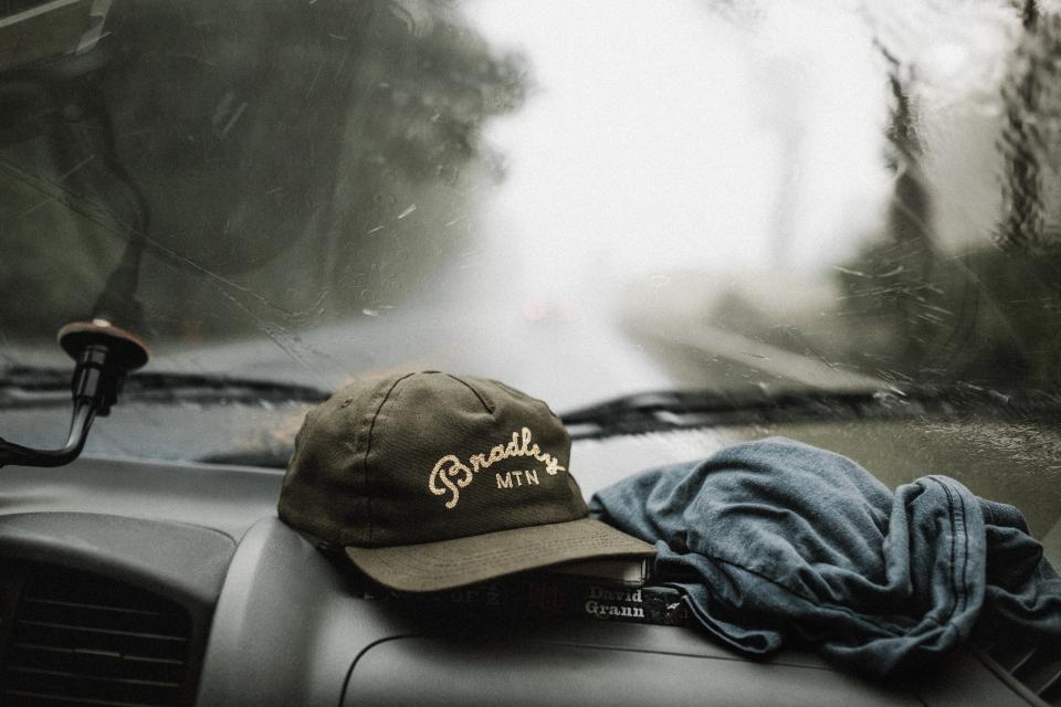 """Dodatek do tekstu: """"Ahoj przygodo! Podróże w pojedynkę"""". Zdjęcie przedstawia widok z przedniej szyby w samochodzie i leżące pod nią: czapkę i chustę. Za oknem widać drogę, po lewej stronie - las. Wszystko otulone jest mgłą."""