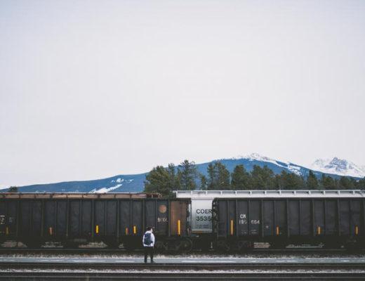"""Dodatek do tekstu: """"Ahoj przygodo! Podróże w pojedynkę"""". Przedstawia wagony i stojącego przed nimi mężczyznę. Za pociągiem widać zarys gór i drzewa stojące opodal. Zdjęcie ma smutny klimat, ale silne nawiązanie do podróży."""